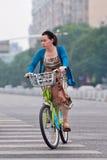 La femme élégante monte un vélo public de part, Pékin, Chine Image stock