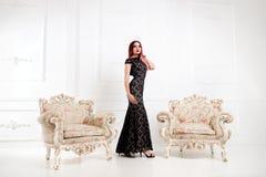La femme élégante ou la fille en égalisant la robe noire se tient dans un a Images libres de droits