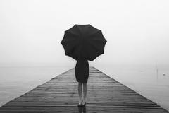 La femme élégante s'est habillée dans la dissimulation noire avec le parapluie photos libres de droits