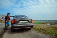 La femme élégante tient la voiture proche sur la route Photo libre de droits