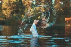 La femme a émergé avec une éclaboussure de l'eau Photographie stock