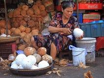 La femme épluche des noix de coco sur le marché en plein air en Hue, Vietnam Photos stock
