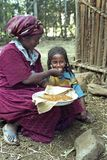La femme éthiopienne donne l'injera de fille pour manger Photographie stock