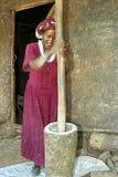 La femme éthiopienne martèle le grain dans la farine photographie stock libre de droits