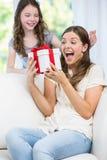 La femme a étonné regarder le cadeau donné par la fille Image stock