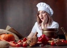 La femme étonnée dans l'uniforme d'un chef lit un vieux livre de cuisine image libre de droits