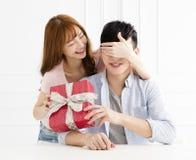 La femme étonne son ami avec le présent à la maison Photographie stock