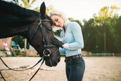 La femme étreint son cheval, amitié, équitation Photo stock