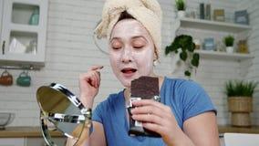 La femme étroite avec le masque sur le visage s'assied au miroir mange de la nourriture malsaine de concept de chocolat banque de vidéos