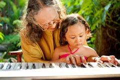 La femme aînée asiatique enseignent l'enfant jouant le piano Images libres de droits