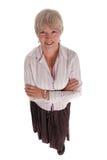 La femme aînée de sourire d'affaires avec des bras s'est pliée Images stock