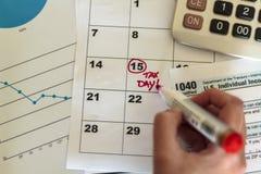 La femme accentuent le jour d'impôts sur le calendrier photographie stock libre de droits