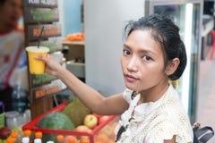 La femme achète la boisson de fruit sur une rue Image stock