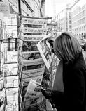 La femme achète un journal allemand de Suddeutsche Zeitung d'un Ne Photo stock