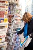 La femme achète un journal français de l'ONU Doigt d'un kiosque à journaux Image stock