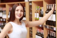 La femme achète le vin de stock Photographie stock