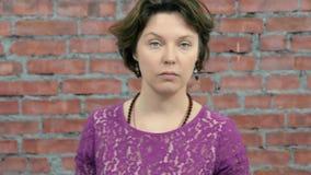 La femme adulte avec les cheveux courts dépeignent le blâme in camera bâti Mur de briques banque de vidéos