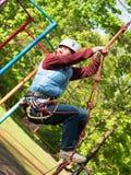 La femme adulte dans un casque et avec un système de sûreté monte une échelle de corde Photos stock