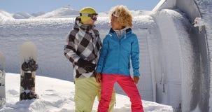 La femme adulte regardant l'ami près fait du surf des neiges Image stock