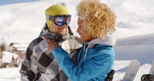 La femme adulte regardant l'ami près fait du surf des neiges Photos libres de droits
