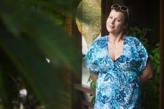 La femme adulte se tient dans la porte de sa maison pendant l'été et attend des invités Paume brouillée l photo libre de droits