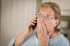 Femme adulte supérieure choquée au téléphone portable dans la cuisine Image libre de droits