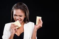 La femme affamée mord la barre du chocolat Photos stock