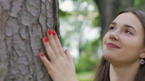 La femme affectueuse aimable caresse les étreintes qu'un arbre recherche, unité avec la nature, unité de la vie banque de vidéos