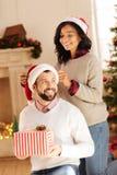 La femme affectueuse ajustant le chapeau de Santa sur ses maris se dirigent Photos libres de droits