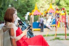 La femme affiche l'eBook contre la zone de terrain de jeu Photo stock