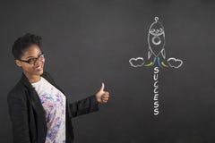 La femme africaine avec des pouces lèvent le signal de main et la fusée de succès sur le fond de tableau noir Photos libres de droits
