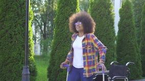 La femme africaine avec une coiffure Afro se lève d'un fauteuil roulant après une blessure banque de vidéos