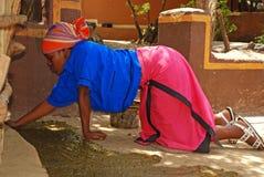 La femme africaine a couvert le plancher de la maison en engrais Photos libres de droits