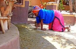 La femme africaine a couvert le plancher de la maison en engrais Photographie stock