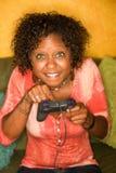 La femme afro-américaine joue le jeu vidéo photos libres de droits