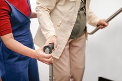 La femme agée à l'aide d'une canne avec la fille font attention photos stock