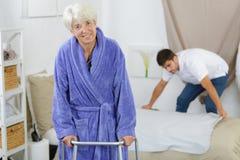 La femme agée ambulates du lit avec le marcheur Image libre de droits