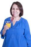 La femme agée boit du jus d'orange Photographie stock libre de droits