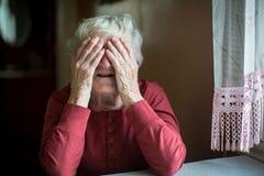 La femme agée couvre le visage de mains froissées aide Images stock