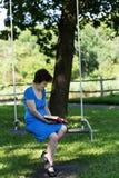 La femme agée dans la robe bleue de point de polka s'assied sur l'oscillation Images stock