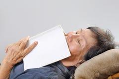 La femme agée est tombée endormi avec le livre Images stock