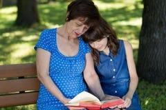 La femme agée et la fille s'asseyent sur le banc et lisent la BO Photographie stock libre de droits