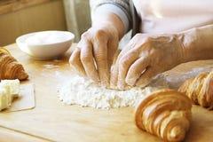 La femme agée fait cuire les croissants français, découvrent les mains froissées, ingrédients, lumière chaude molle de matin, vue Images libres de droits