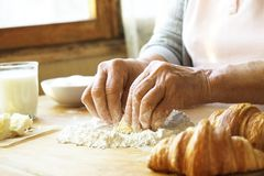 La femme agée fait cuire les croissants français, découvrent les mains froissées, ingrédients, lumière chaude molle de matin, vue Photographie stock