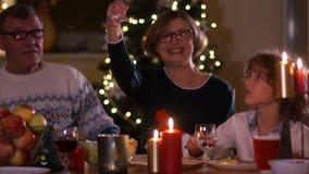 La femme agée heureuse avec la famille soulève un verre à la table de Noël Décorations de Noël, bougies sur la table banque de vidéos