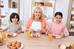 La femme agée heureuse dine avec ses petits-enfants à la table de dîner dans la cuisine Image stock