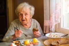 La femme agée mangent la séance à la table de dîner photo libre de droits