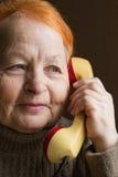 La femme agée parle au téléphone rétro Images stock