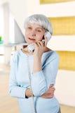 La femme agée parle du téléphone Photographie stock libre de droits