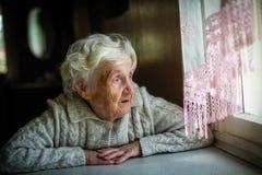 La femme agée repose et regarde la fenêtre images stock